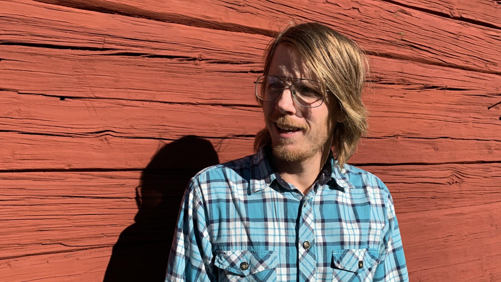 Josh Armfield med en rödmålad ladvägg i bakgrunden.