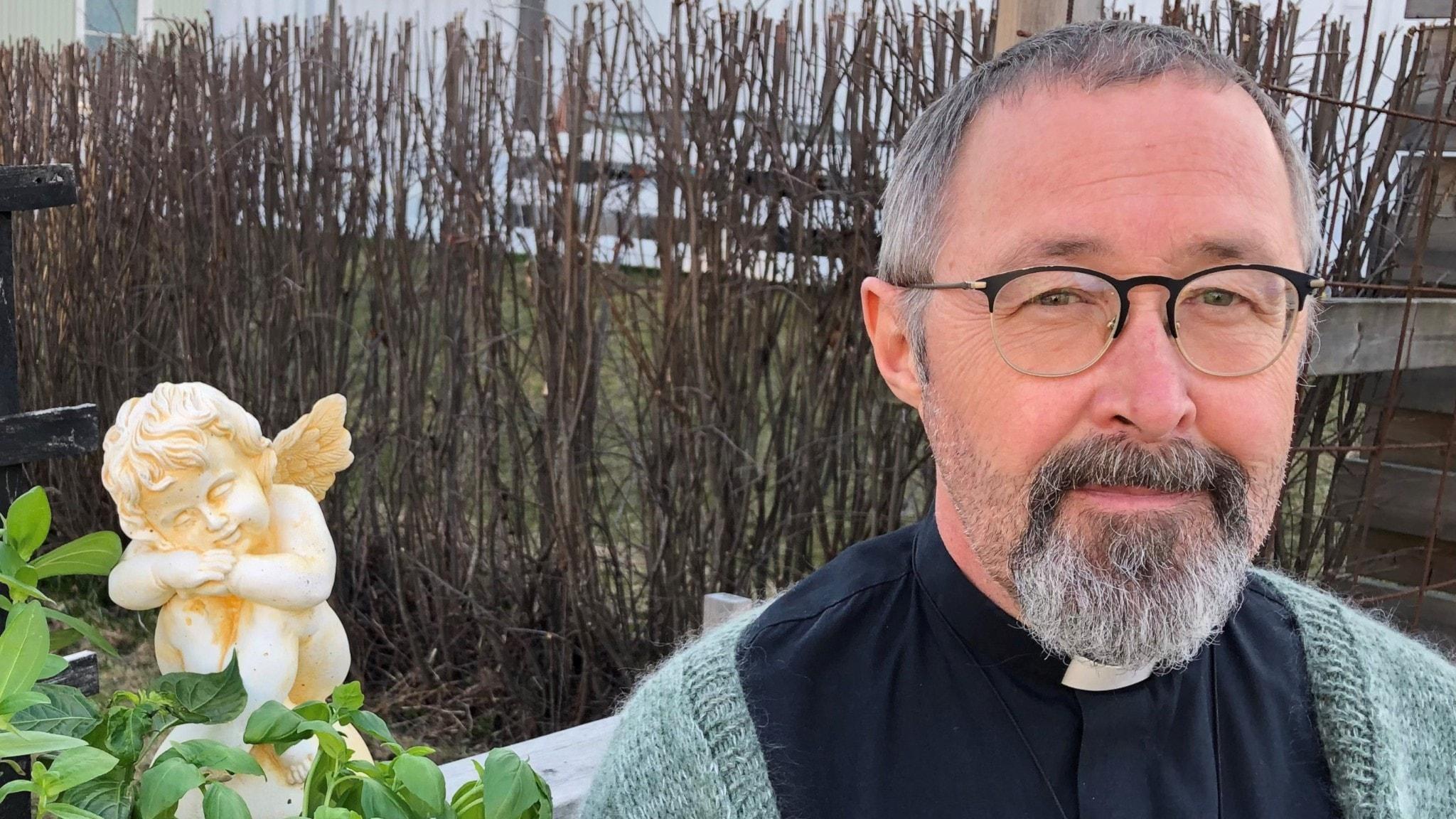 Lars Segerstedt i prästkrage och en gröngrå kofta. Han bär hornbågade glasögon och är gråsprängd i skägget.
