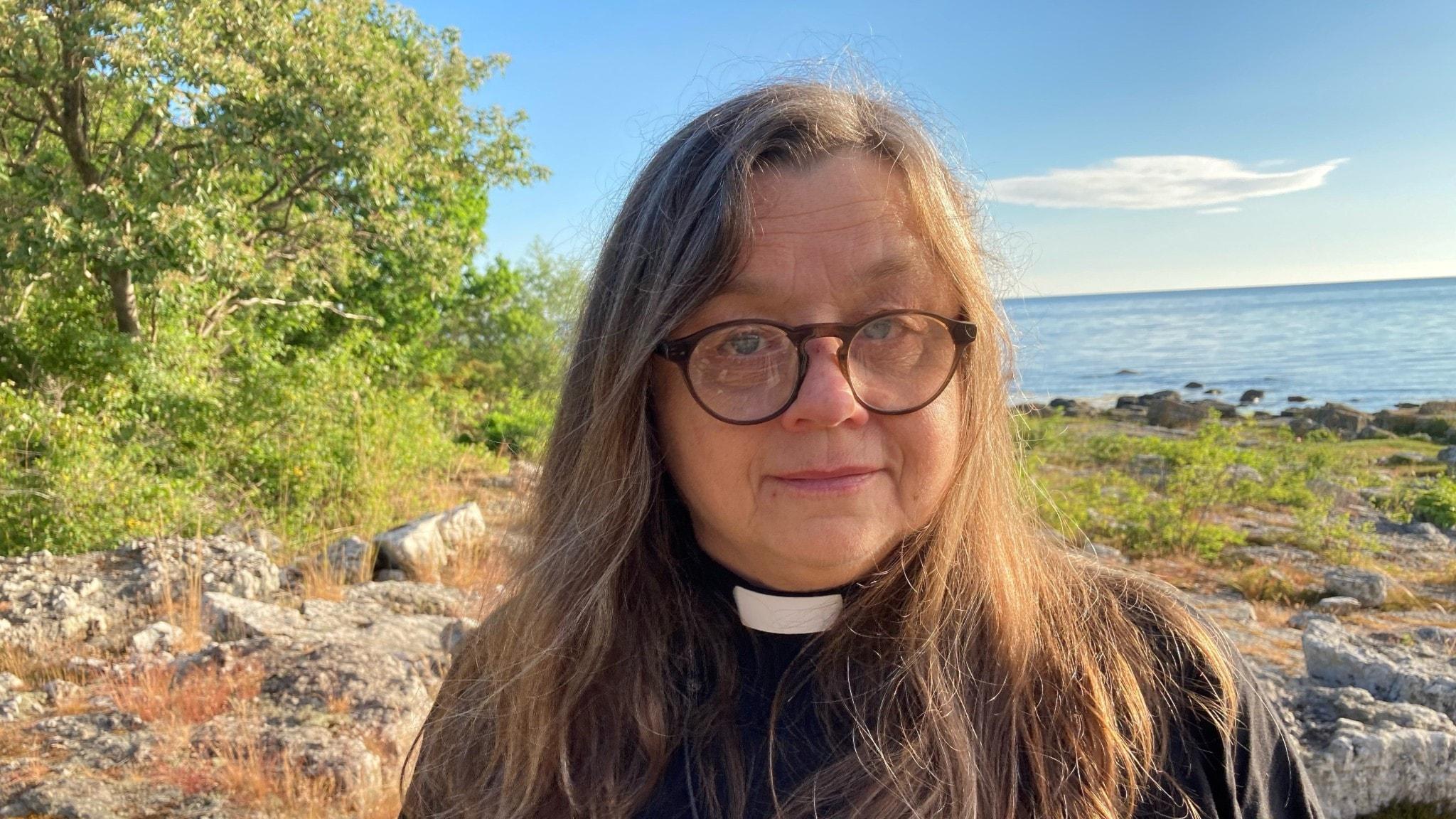 En kvinnlig präst på en strand