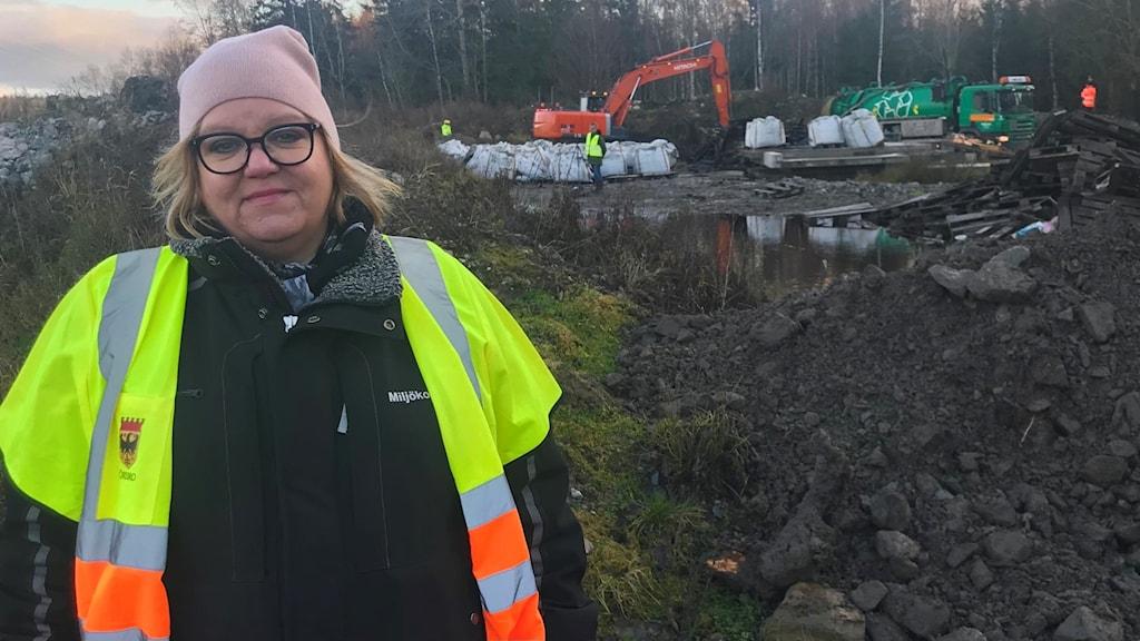 Johanna Elving vid platsen där svartmassa grävts ner i jorden. I bakgrunden jobbar en grävmaskin