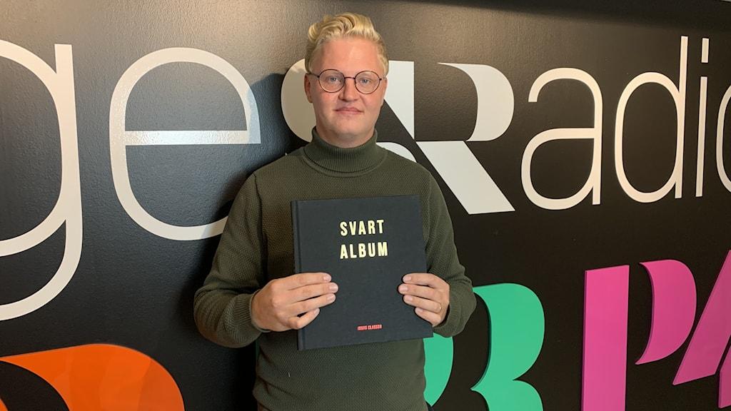 Fågelfotografen Jonas Cleasson håller i sin nysläppta bok Svart Album.