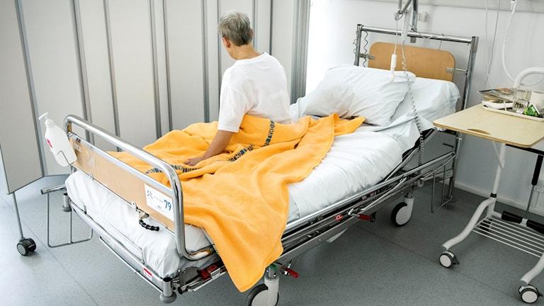 En sjuk kvinna sitter på en säng på ett sjukhus