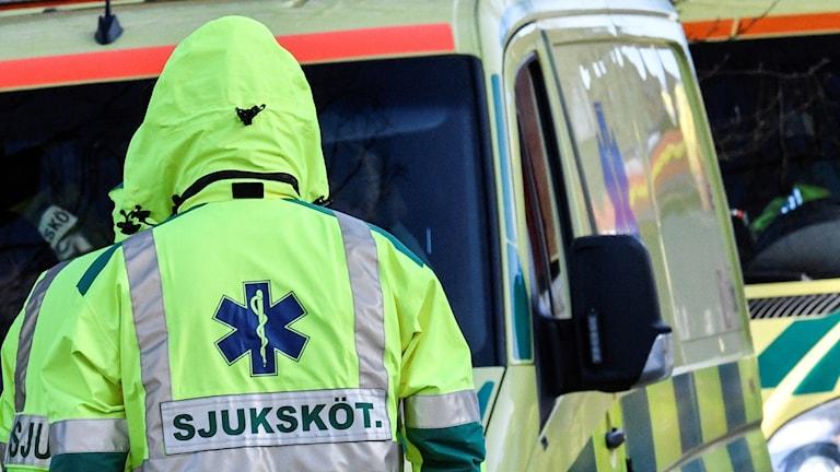 Ambulanspersonal framför fordon.