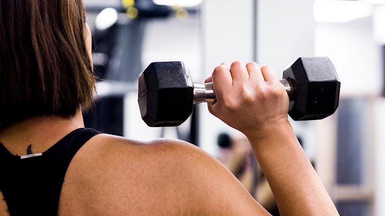 Bild på en kvinna som styrketränar genom att lyfta en hantel.