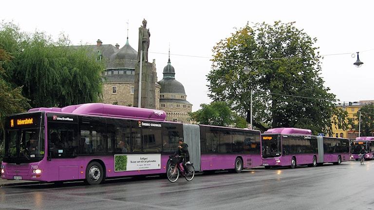 Stadsbussar och en cyklist framför Örebro slott. Foto: Sandra Nielsen/SR Örebro.