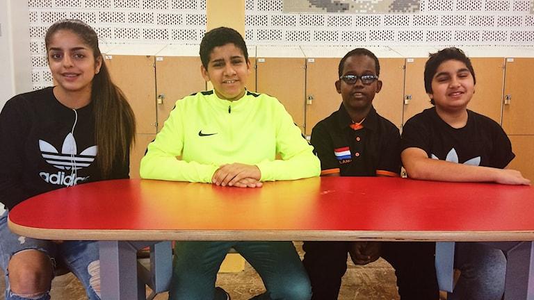 Elever på Lillåns skola som sitter vid ett bord i entrén och ler in i kameran.