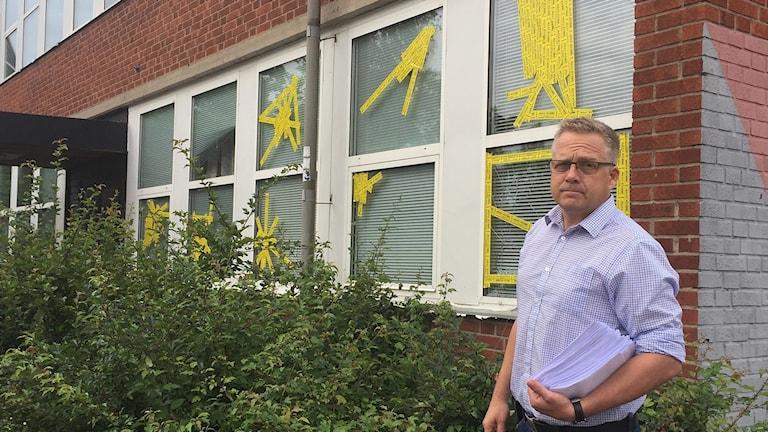 Rektor Peter Svensson står med flygbladen i famnen framför Skrantaskolan.