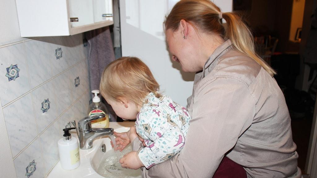 Cecilia hjälper snart 2-åriga Edda att tvätta händerna i handfatet.