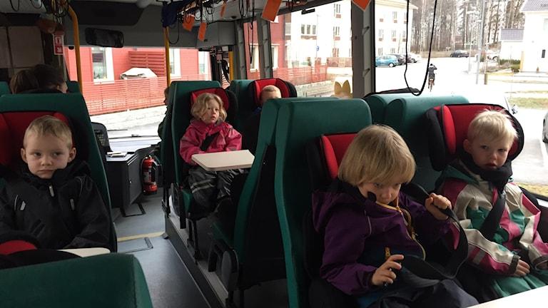 Barnen gör sig beredda att rulla iväg med förskolebussen.