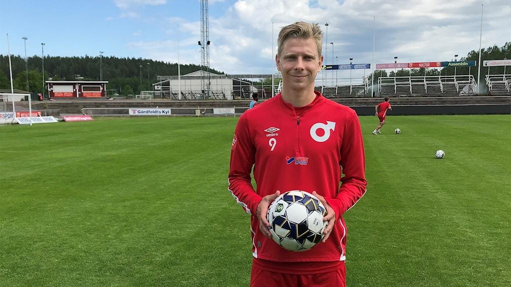 Johan Bertilsson står på Stora Vallas gräsplan. Foto: Viktoria Svärd Karlsson/Sveriges Radio.