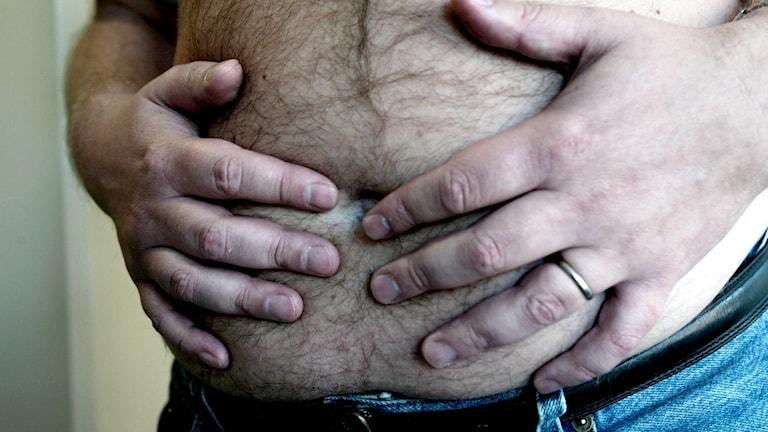 Fet man håller sig för magen.