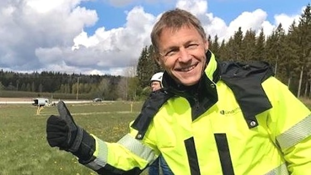 Man i gula arbetskläder tittar glatt in i kameran och gör tummen upp. Mannen är Linde energis VD Jens Isemo.