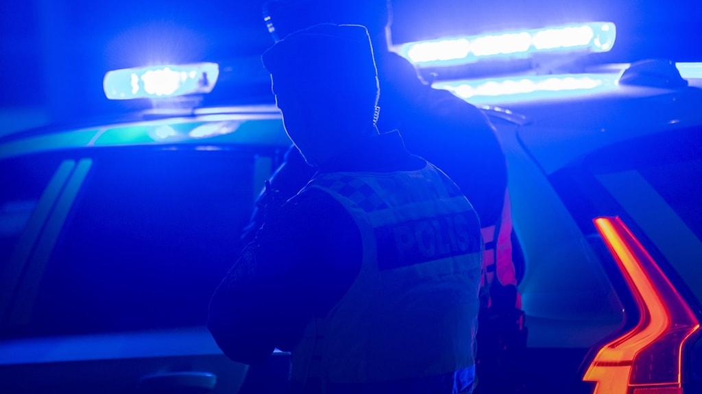 Poliser med bil en mörk kväll