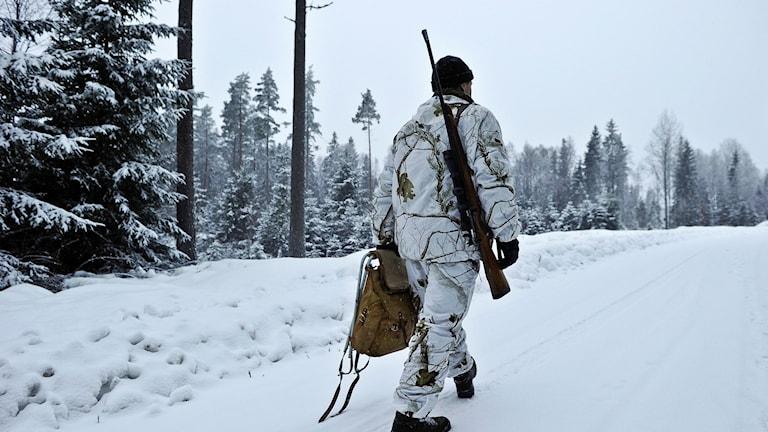 En viktklädd jägare går på en väg med geväret över axeln.