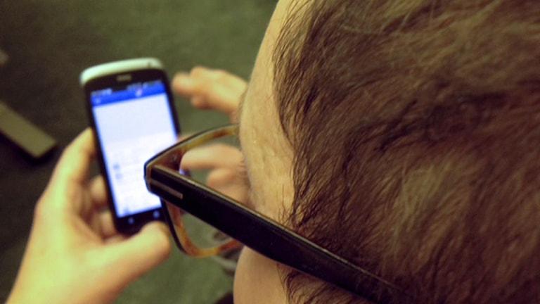 Man med mobiltelefon i handen.