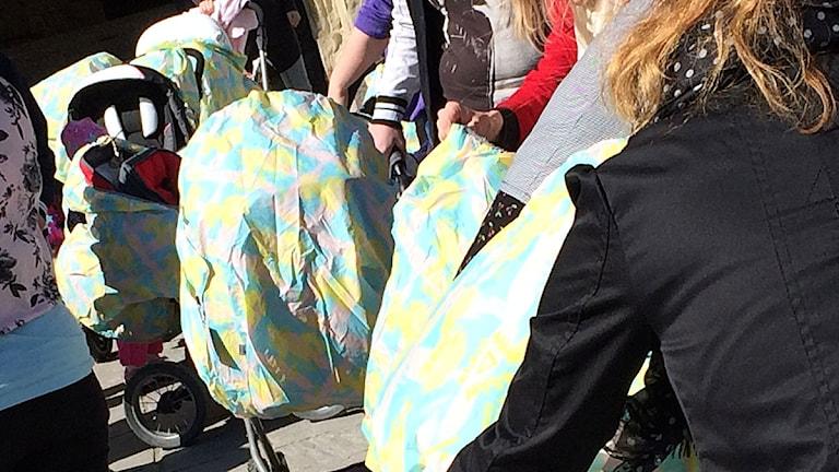 Barnvagnarna kläds med pastellfärgade regnskydd. Foto: Madde Klippel/Sveriges Radio