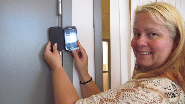 Camilla Johansson visar hur man håller upp mobilen mot klisteretiketten. Foto: Anna Björndahl/Sveriges Radio.