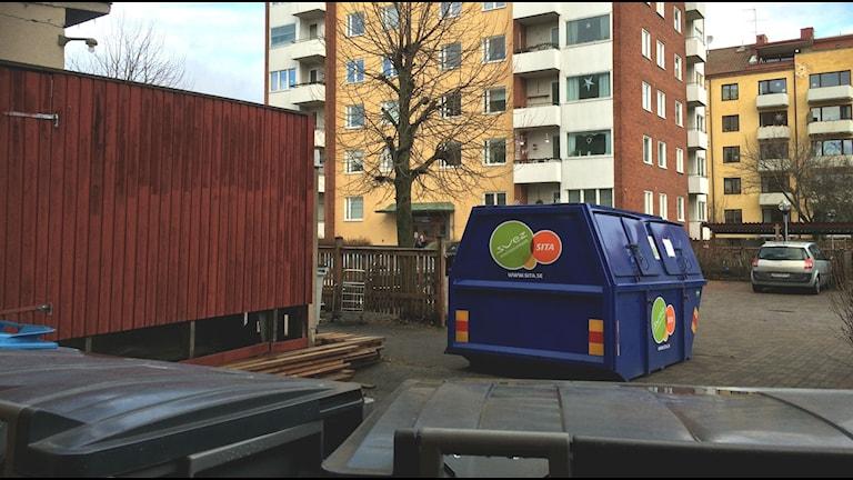 De som bor i husen där borta får gå till sopbehållarna i förgrunden för att slänga kartong. Foto: Anna Björndahl/Sveriges Radio.