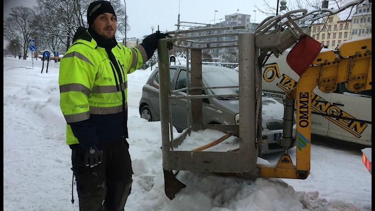 Isac Agnesson Frullas arbetsplats är inuti korgen som hissas upp till taket. Foto: Anna Björndahl/Sveriges Radio.