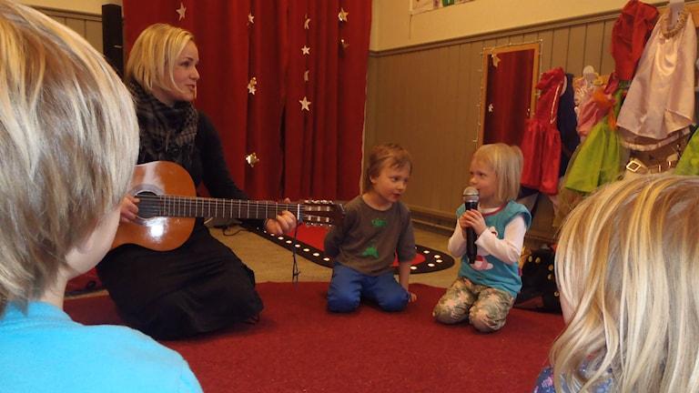 Sångstund på förskolan Terra Nova. På bilden från vänster Anna Kahl med gitarr, Zion Juuska och Alma Lindh vid micken. Foto: Martina Lindh.