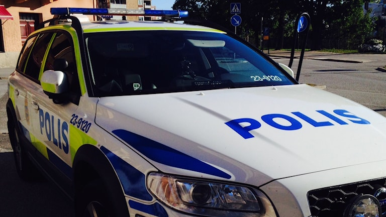 En polisbil står parkerad i en korsning.