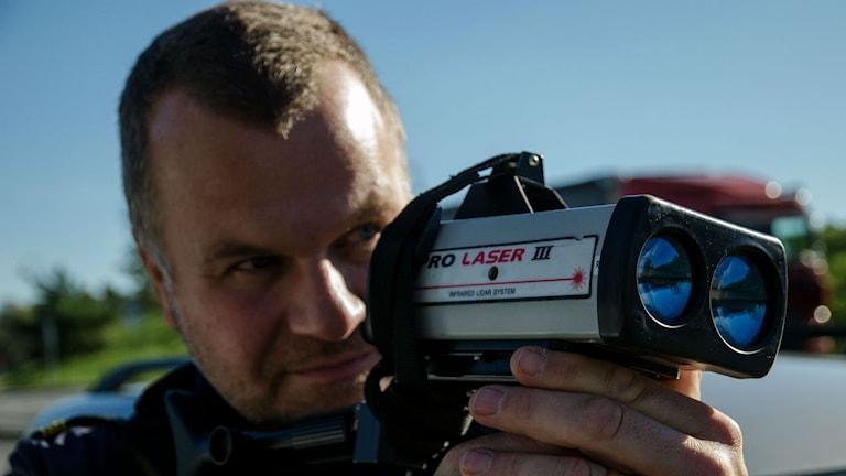 Trafikpolisen Christer Andersson mäter hastigheten på E18/E20.
