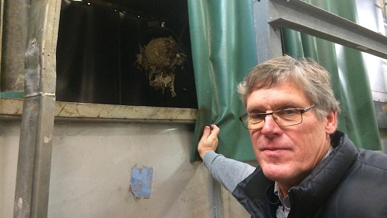 John Harfeldt bredvid containern där avfallet samlas. Foto: Anna Björndahl/Sveriges Radio.
