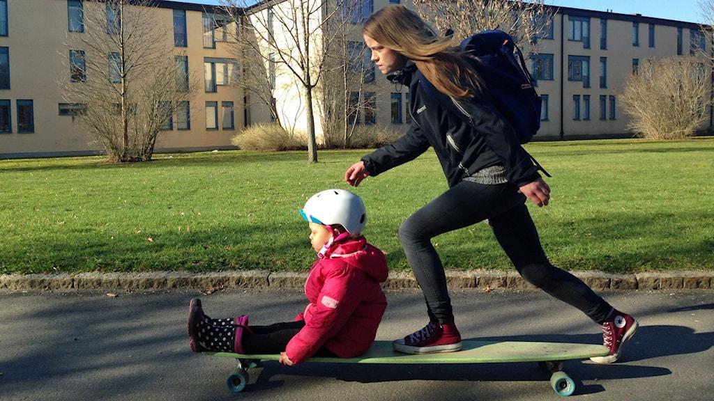Lisa Åsell och dottern Fatima på väg på longboard till förskolan.