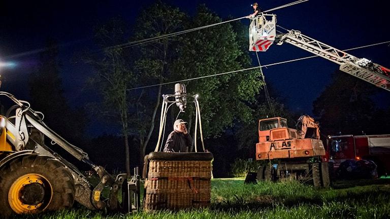 Ballongkorg med man stående i på natten i gräs.