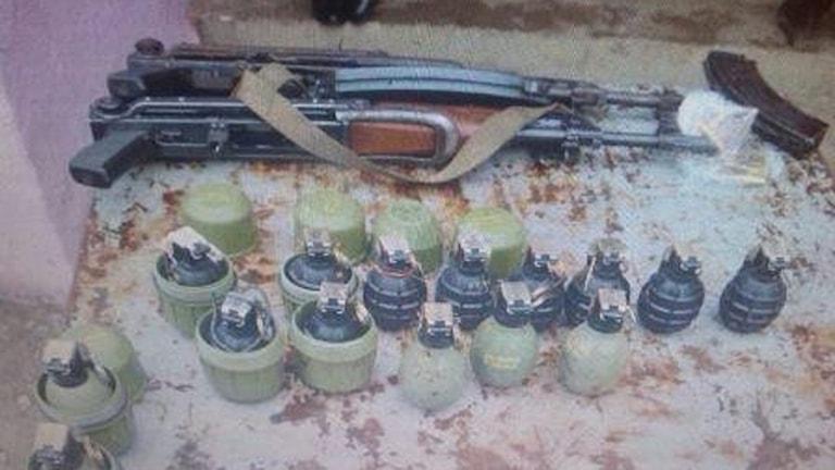 gevär och granater ligger på ett bord