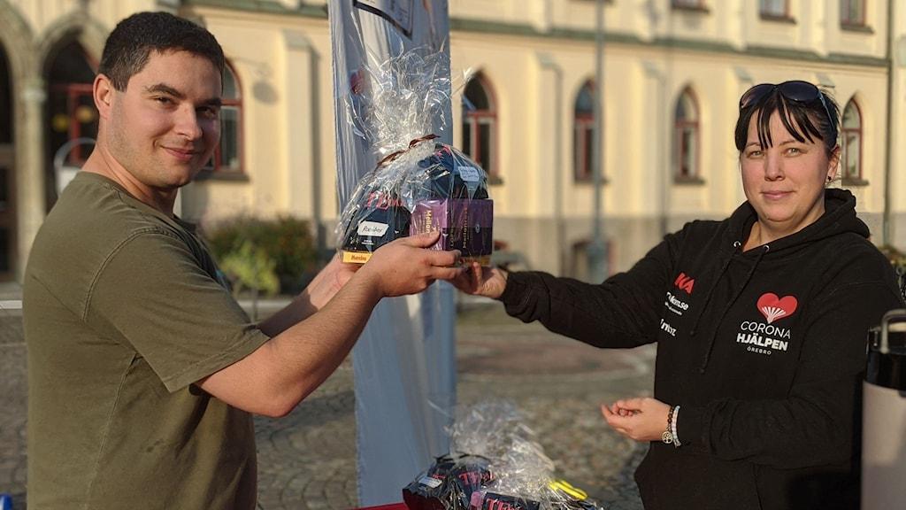 Volontären Rasmus Oldin får en gåva av Zannah Söderlind på Coronahjälpen Örebro.