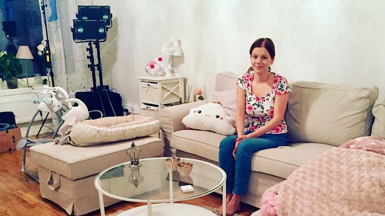 Linn Andersson hemma i soffan. I hörnet står TV-utrustning som används vid inspelningen av Unga mammor.