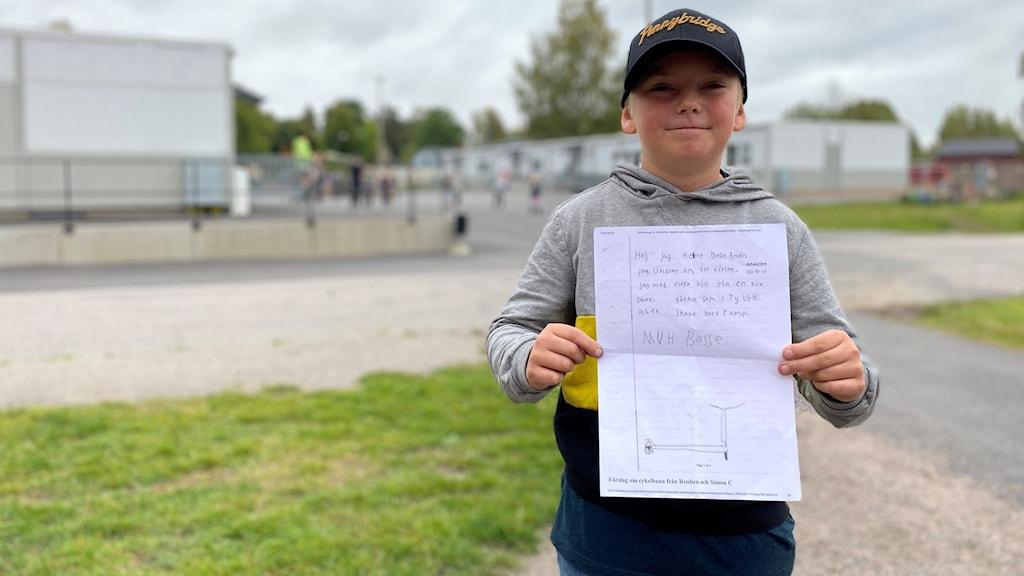 """10-åringen Sebastian """"Basse"""" Brodin står på en skolgård i Lekeberg och visar upp sitt medborgarförslag på papper."""