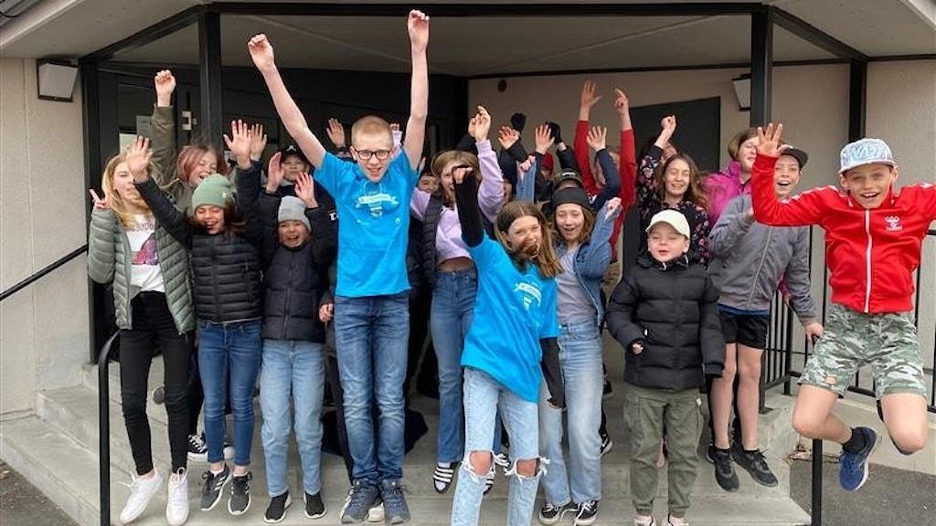 Klassen står under ett tak som finns vid utgången av Lillåns skola. Flera av eleverna hoppar upp i luften, andra höjer sina armar.