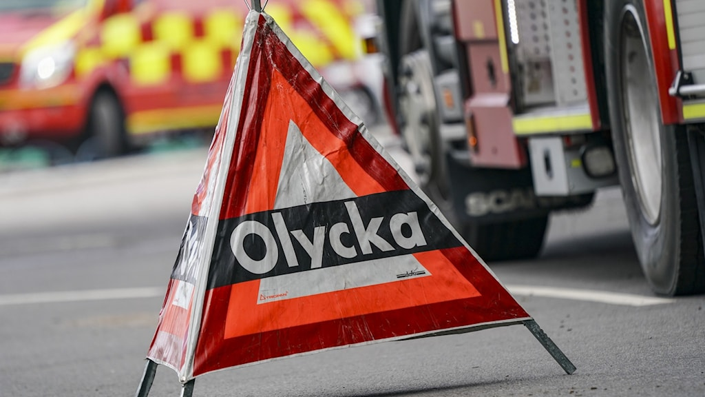 Triangel med texten olycka, fordon från räddningstjänsten i bakgrunden. Foto: Johan Nilsson/TT