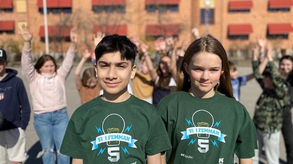 Shayan och Ebba är iklädda varsin grön Vi i femman-tröja. De står på skolgården, bakom dem syns några av klasskamraterna som står en bit bort.