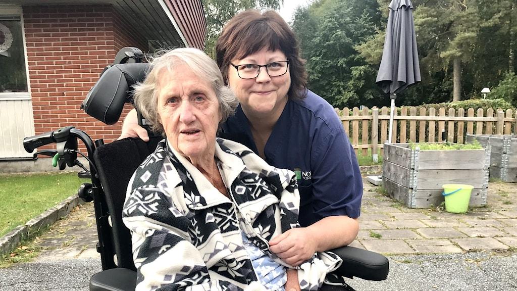 Bild på Ingegerd Gustavsson som är boende på Hagby Ängar i Nora tillsammans med undersköterskan Kristina Lockander. Kristina står bakom Ingegerd som sitter i rullstol.