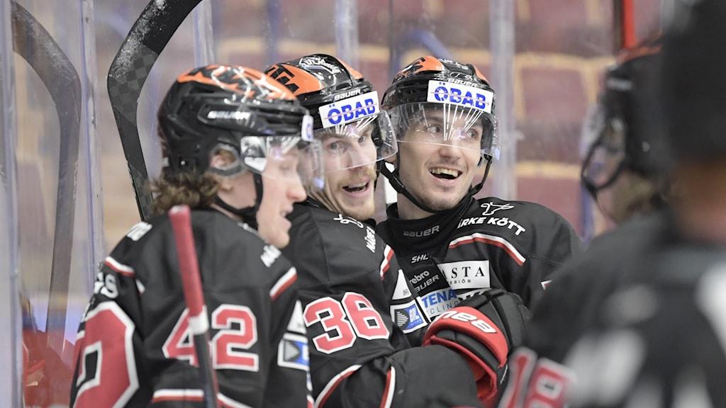 Tre spelare från Örebro ser glada ut och klappar om varandra. En domare skymtar i förgrunden. Foto: Ulf Palm/TT