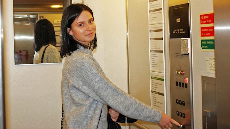 Izabelle Grynthal står framför en hissdörr.