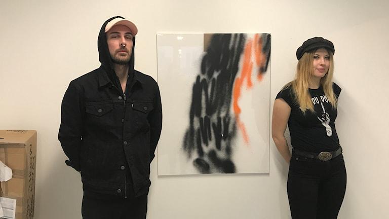 Fredrik Landevaag och Lovisa Kjellsdotter framför ett av konstverken