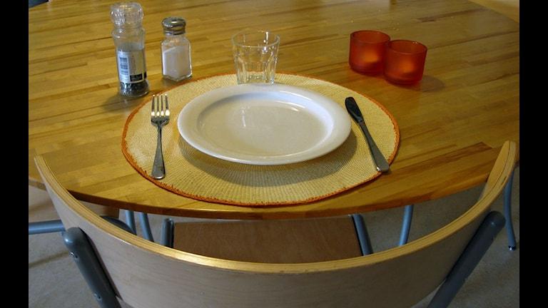 En tom tallrik står på ett bord. Glas och bestick, salt och peppar. Foto: Anna Björndahl/SR.