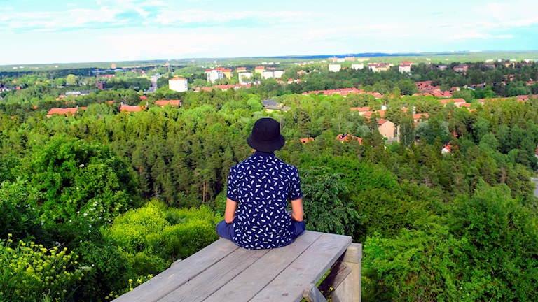 Ensam person med hatt sitter på träbryggan och blickar ut över grönskan och bebyggelsen.
