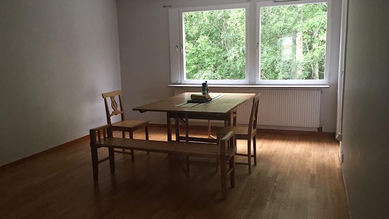 Vardagsrummet har inretts med ett bord, två stolar och en bänk. Punkt.