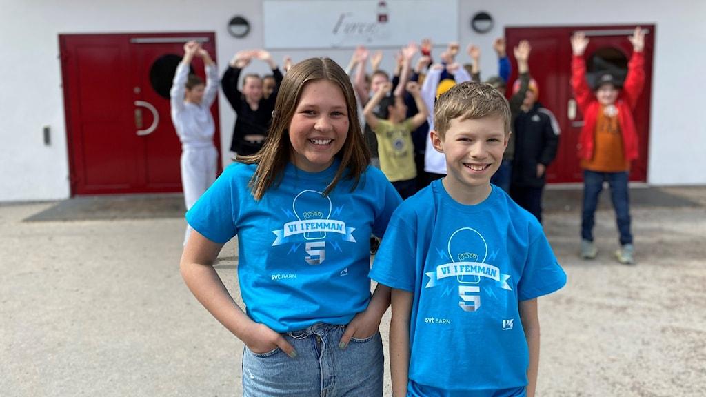 Linnea och Erik står på skolgården iklädda varsin Vi i femmantröja. Resten av klassen står i bakgrunden och vinkar.