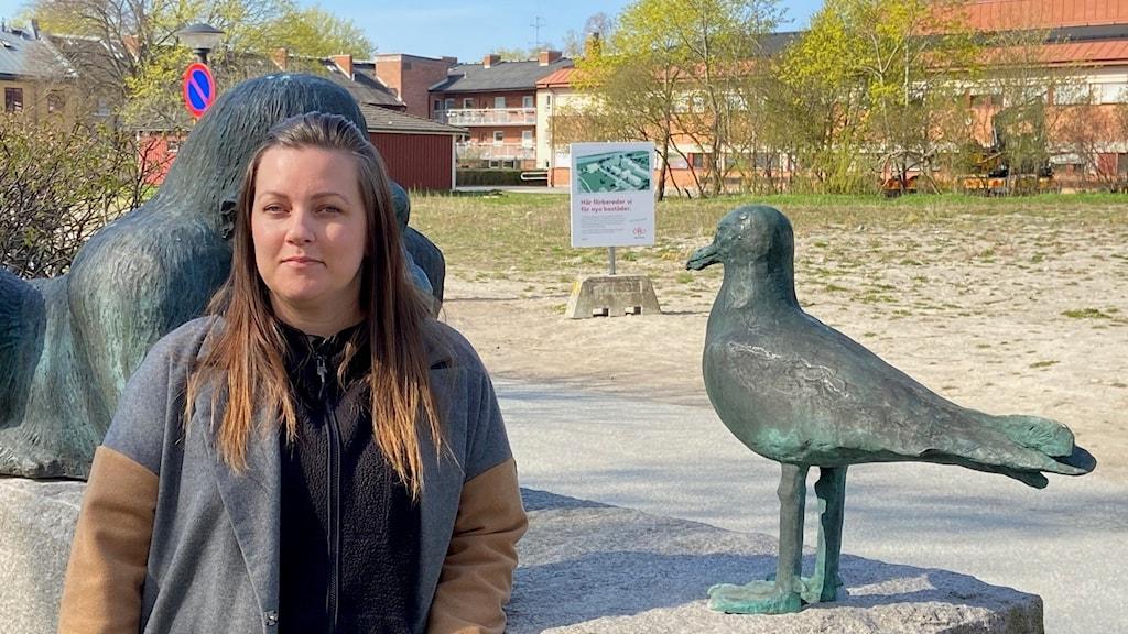 Sanna Bolinder står vid en staty av en mås vid tomten i kvarteret Måsen som ska bebyggas.
