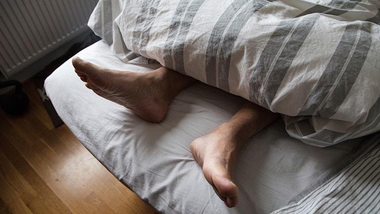 Fötter som sticker ut under täcke i säng