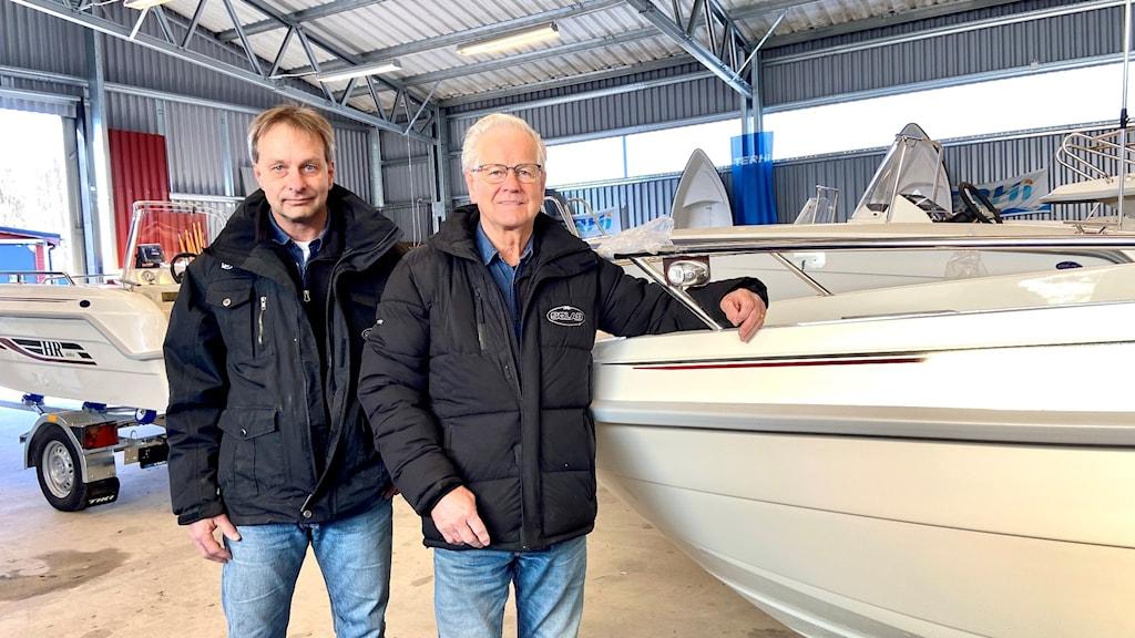 Jens och Sven-Olof framför en båt i en hall.