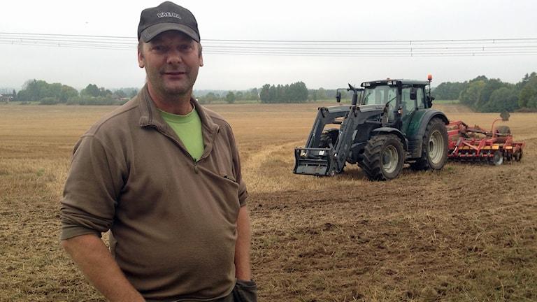 Per Willén står på sin åker framför en traktor.