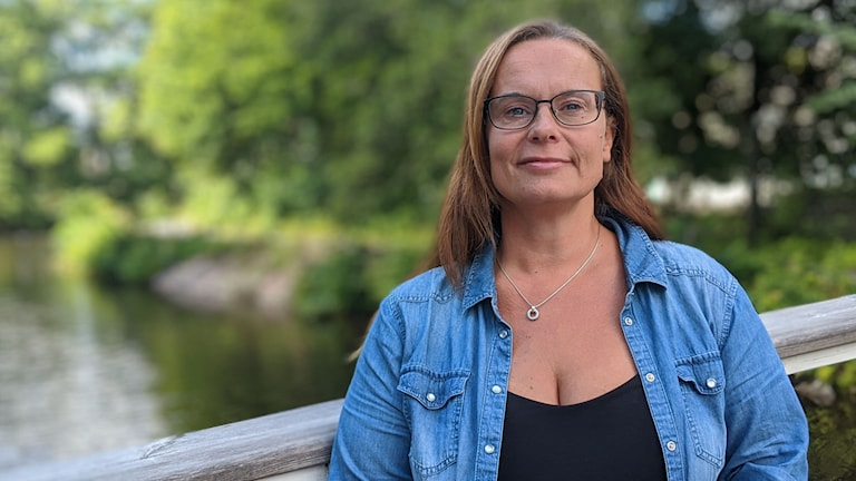 Sanna Aila Gustafsson som är enhetschef på Eriksbergsgården står och lutar sig mot räcket på en bro. Det är en grön och somrig bakgrund.