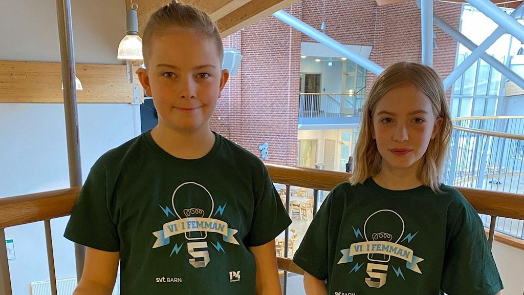 Axel och Siri står på en balkong i skolan iklädda varsin grön Vi i femman-tröja.
